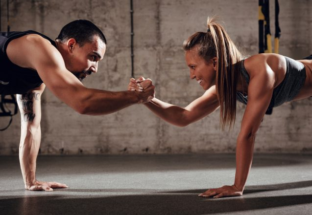Young muscular couple doing strength exercise at the cross fit workout.